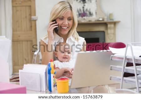 Mother and baby in home office with laptop and telephone - stock photo