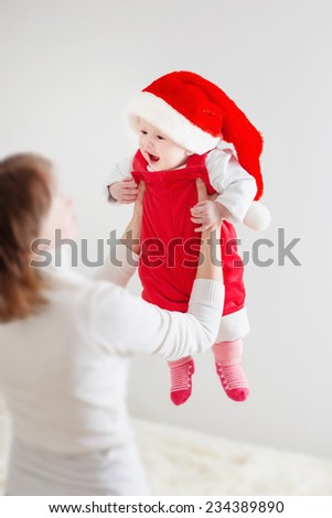 mother and baby in red Christmas hat - stock photo