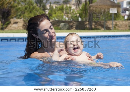 mother and baby in swimming pool laughing - stock photo