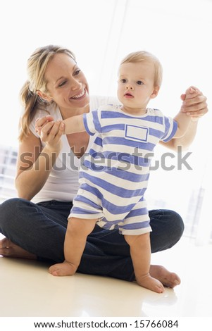 Mother and baby indoors playing and smiling
