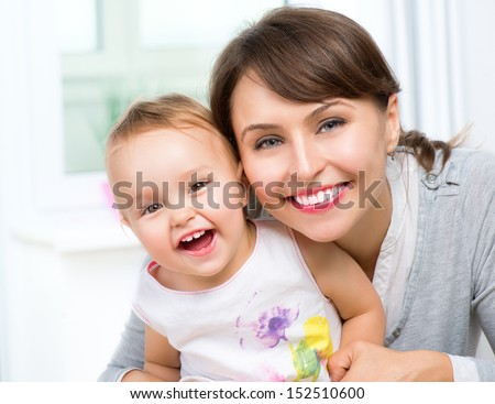 Mother and Baby kissing and hugging at Home. Happy Smiling Family Portrait - stock photo