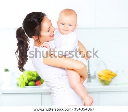 Mother and Baby kissing and hugging at Home. Happy Smiling Family Portrait. Happy Family. Mom and Her Child Having Fun together in the kitchen, diet,dieting concept. Healthy eating