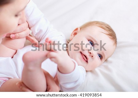 Mother and baby kissing, laughing and hugging.Happy cheerful family. - stock photo