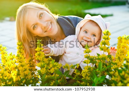 mother and baby looking at camera behind flowers in the garden with warm sunlight - stock photo