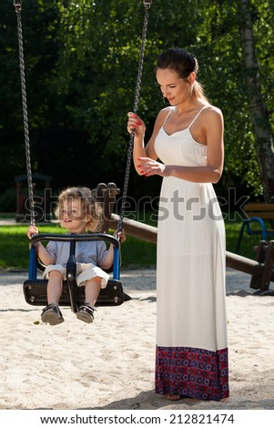 Mother and baby on the playground, vertical