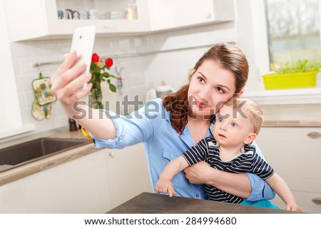 Mother and baby photographing selfie themselves by mobile  - stock photo