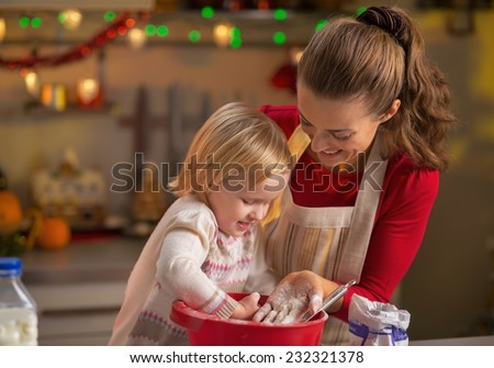 Mother and baby playing while making christmas cookies in kitchen - stock photo