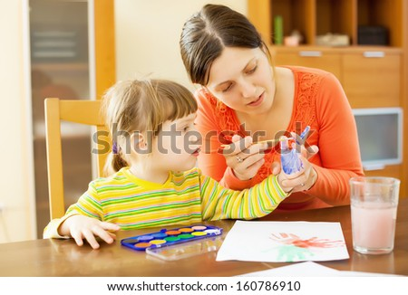 mother and baby  plays with watercolor in home interior