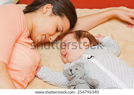 Mother and baby quietly sleeping together on the bed.