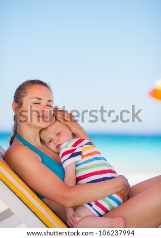 Mother and baby relaxing on sunbed on beach - stock photo