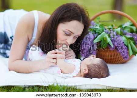 mother and baby resting in summer park - stock photo