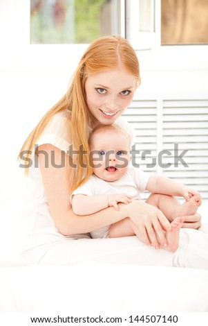 Mother and baby sitting, smiling
