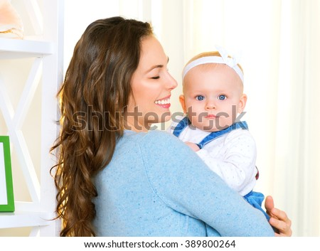 Mother and Baby smiling together. Love. Happy cheerful family Mom and Baby girl kissing and hugging at home. Beautiful healthy mother and little daughter. Maternity concept. Parenthood. Motherhood  - stock photo