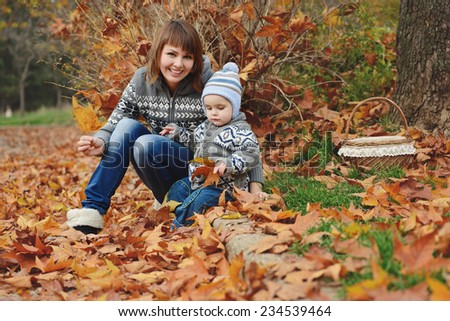 mother and baby son in fall having fun