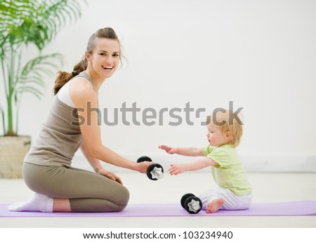 Mother and baby spending time in gym - stock photo