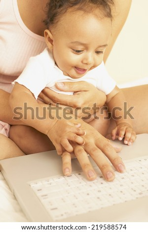 Mother and baby using laptop together - stock photo