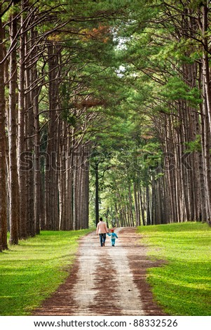Mother and baby walk on country rural road in pine forest - stock photo