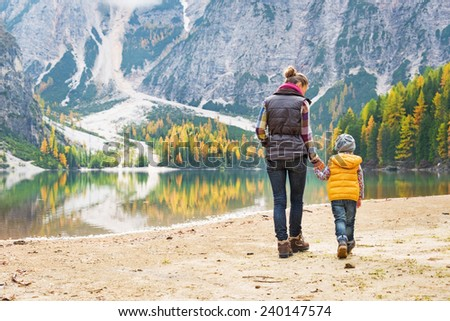 Mother and baby walking on lake braies in south tyrol, italy. rear view - stock photo