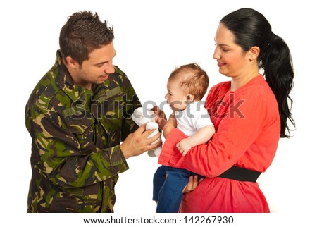 Mother and baby welcoming military father who gives to his child a fluffy bear toy isolated on white background