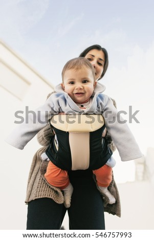 Mother and baby with carrier kangaroo. Outdoor image of family lifestyle.