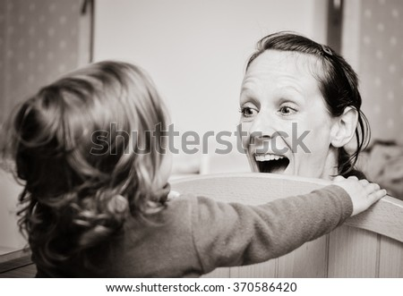 Mother and child are playing peekaboo or peek-a-boo on a children bed and having fun. - stock photo