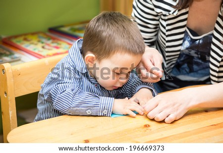 Mother and child boy drawing together with color pencils in preschool at the table in kindergarten
