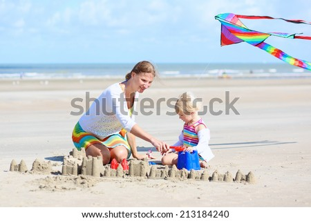 Mother and child concept: young beautiful woman and her lovely cute toddler daughter playing together on the beach building sand castles and flying colorful kite, North Sea, Belgian coast - stock photo