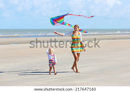 Mother and child concept: young beautiful woman and her lovely cute toddler daughter playing together on the beach flying colorful kite at the sea - stock photo