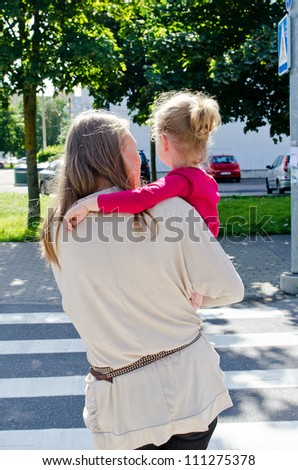 Mother and child crossing the road. Back view. - stock photo