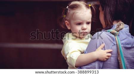 Mother and child,cute little girl resting on her mother's shoulder, vintage filter effect,selective focus