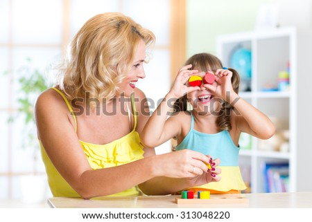 Mother and  Child Daughter Have Fun Playing with Toys - stock photo