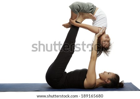 Mother and child doing yoga together in a fitness studio - stock photo