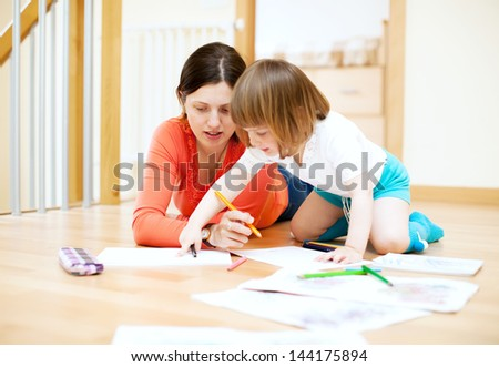 mother and  child drawing on paper at parquet floor. Focus on woman only - stock photo