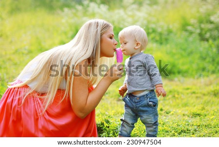 Mother and child eating ice cream outdoors in summer day - stock photo