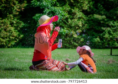 Mother and child from Asia play bubble on a park in Canada