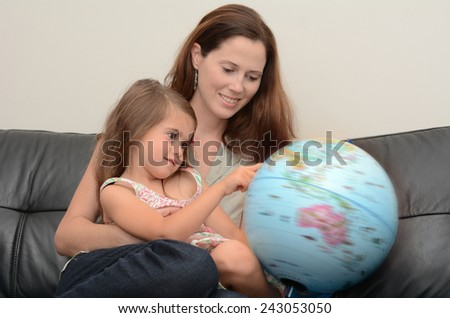 Mother and Child (girl age 05) search and examining the Globe  at home. Concept photo travel and education - stock photo