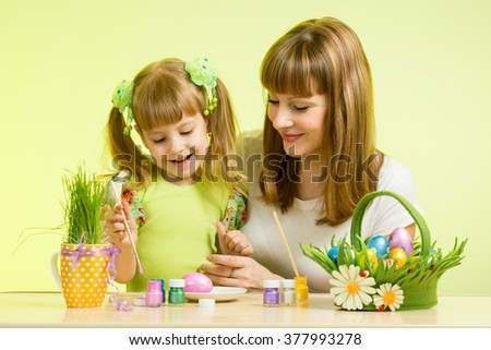 mother and child girl paint eggs preparing to Easter holiday - stock photo