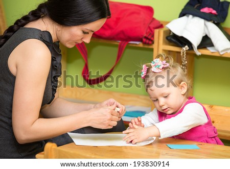 Mother and child girl playing in kindergarten in Montessori preschool Class. - stock photo