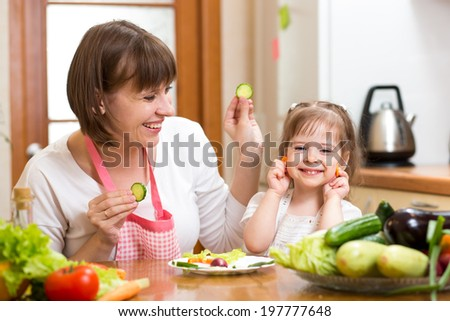 mother and child girl preparing healthy food and having fun - stock photo
