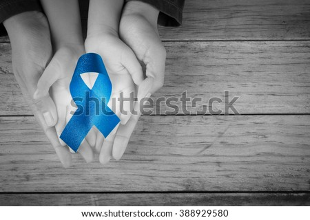 Mother and child hand hold blue ribbon awareness colon colorectal cancer  Awareness loop symbolic logo raising support help people life living - stock photo