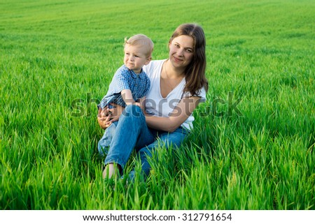 Mother and child having fun sitting on the green grass