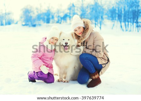 Mother and child hugging white Samoyed dog in winter day - stock photo