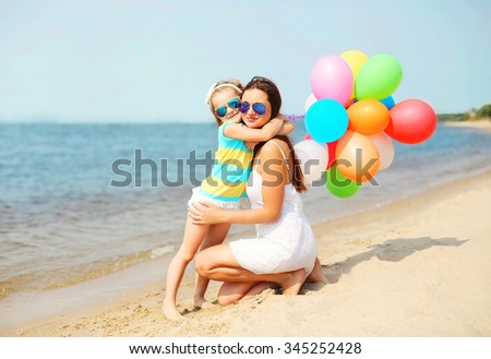 Mother and child hugging with colorful balloons on beach near sea - stock photo