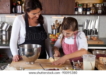 Mother and child in the kitchen baking together - stock photo
