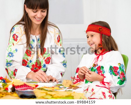 Mother and child in Ukrainian national cloth doing crafts