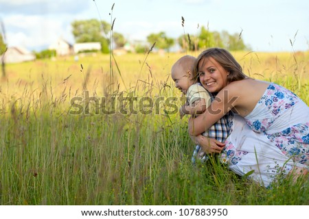 mother and child on summer field - stock photo