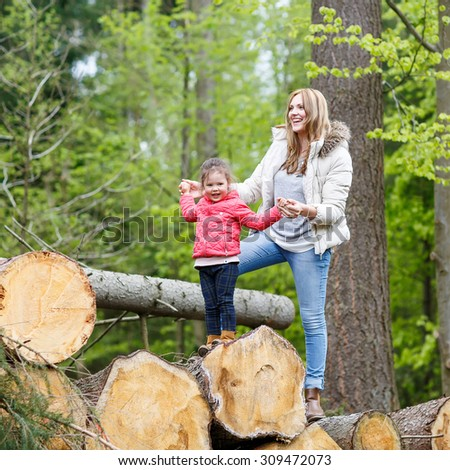Mother and child outdoors playing, kissing and hugging. Happy family of two, young smiling woman and her cute toddler daughter enjoying beautiful day in the forest