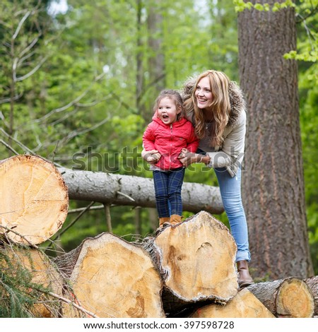 Mother and child outdoors playing, kissing and hugging. Happy family of two, young smiling woman and her cute toddler daughter enjoying beautiful day in the forest - stock photo
