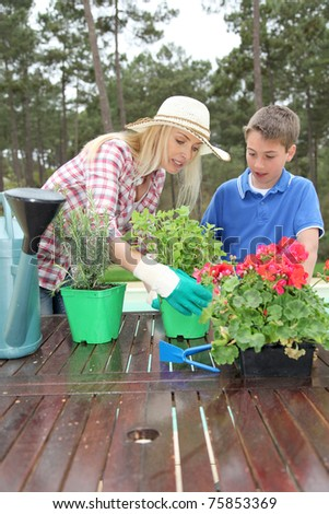 Mother and child planting flowers in house garden