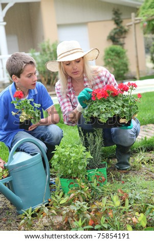 Mother and child planting flowers in house garden - stock photo